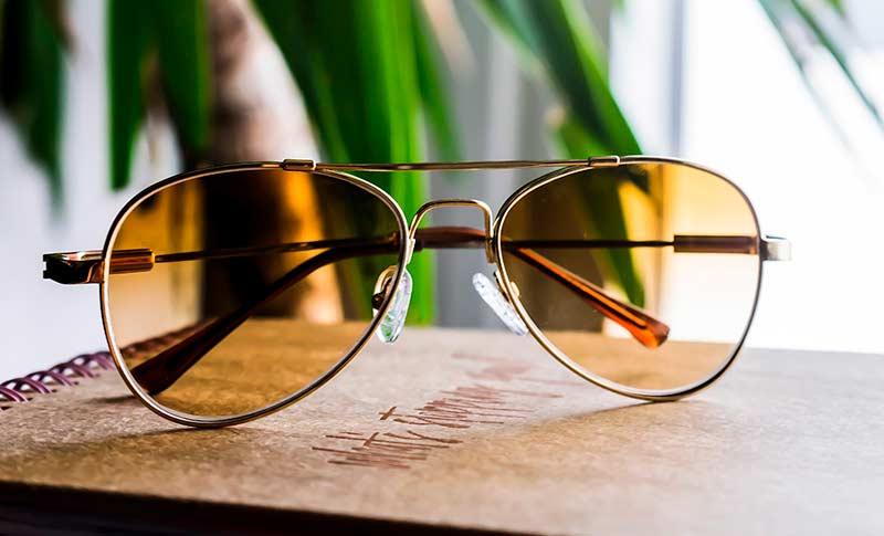 pilotsolbriller med gule glass som ligger på en bok foran en plante