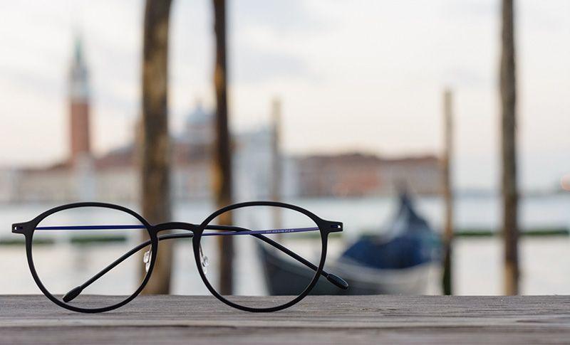 briller som ligger på et bord med sjø i bakgrunnen