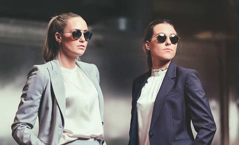 to jenter med dress og runde solbriller