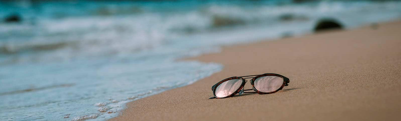 solbriller som ligger på en strand